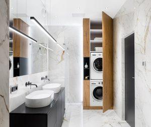 Tesla mašina za pranje veša i Tesla mašina za sušenje veša u zatvorenoj drvenoj polici u velikom kupatilu