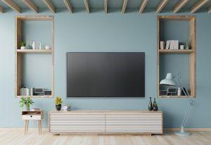 dekorativni plavi zid sa drvenim policama i Tesla televizorom