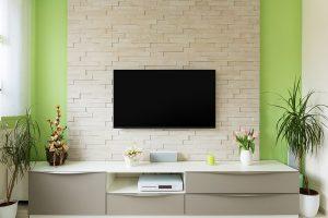 dekorativni zid sa svetlim ciglama sa Tesla televizorom