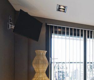 Tesla televizor postavljen u uglu sobe na zglobni nosač za TV
