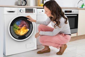 Mlada žena gleda odeću koja se rotira unutar Tesla mašine za pranje veša u kuhinji kod kuće.
