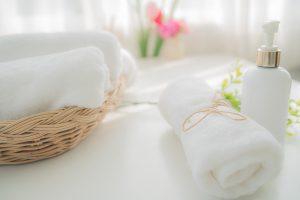 Beli peškir pored boce sa tečnim sapunom u kupatilu. Koncept higijene i zdravog života. Izbliza, selektivni fokus