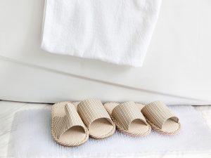 dva para krema papuča na beloj prostirci za kupatilo