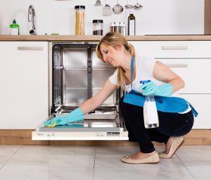 Žena čisti Tesla mašinu za sudove rukavicama i sredstvom za dezinfekciju u kuhinji