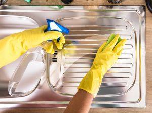 Osoba u žutim rukavicama čisti sudoperu sredstvom za dezinfekciju