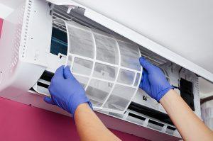 Čišćenje filtera Tesla klima uređaja. Osoba u plavim rukavicama vadi filtere iz Tesla klime