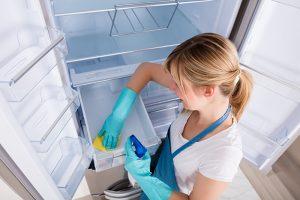 Žena čisti prazan Tesla frižider u plavim rukavicama i sa sredstvom za dezinfekciju
