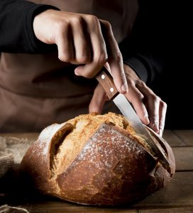 Čovek u kecelji velikim nožem seče domaći hleb. Tamna pozadina