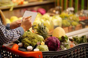 Žena u marketu drži spisak namirnica za kupovinu. Korpa je puna različitih namirnica.