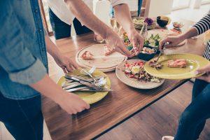 Izbliza izrezana fotografija ljudi koji posle zabave sređuju sto sa hranom. Rade to zajedno, da bi bili brži i zabavniji
