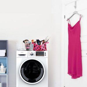 Roze haljina okačena na vrata kupatila. Pored je Tesla veš mašina sa neseserima sa šminkom na njoj.