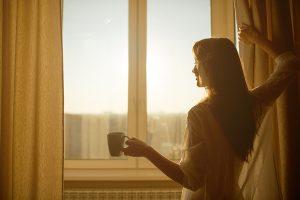 devojka ispred prozora pije kafu na prvom jutarnjem suncu